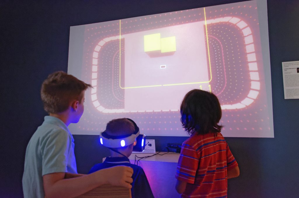 Three children play an interactive, technology-based art game in the Jepson Center's TechSpace gallery.